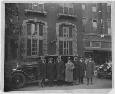 Dean F. Paul Anderson, fourth from the left with a walking stick with unidentified men in downtown Lexington.  Keller Florist is in the background