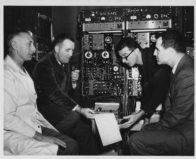 Dr. Fogle Clark, University of Kentucky professor of psychology (second from right), explains electronically - computed data on chimpanzee training to two consultants of Project Mercury, a federal government space project; dr. Joseph Brady (second from left) and Dr. Charles Fester (right), check the progress of four chimpanzees being trained for the Air Force in the University of Kentucky Wenner - Gren Aeronautical Research laboratory; At left is Dr. Karl O. Lange, director of the project and the laboratory
