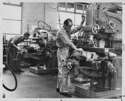 Men using a metal drill press and a metal turning lathe; Photographer: Ben L. Williams, Jr