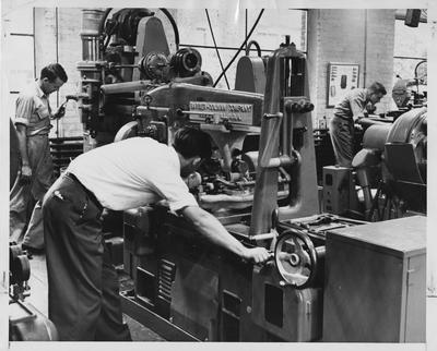 Men using machines to work with metal in the machine shop; Photographer: Ben L. Williams, Jr