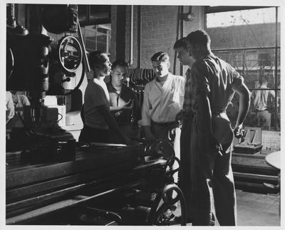 Men stand near a drill press