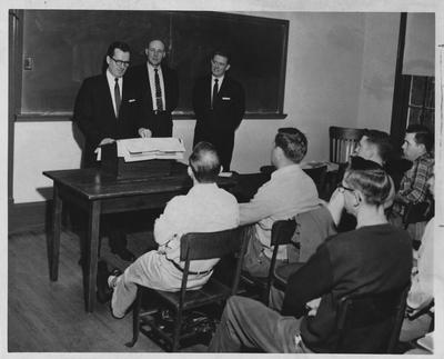Men speaking before a class; From left to right standing: Russ Scofield, W. Farra McDowell, and Ed Moores