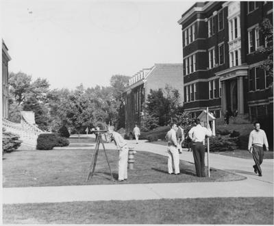 Men surveying in front of Pence Hall