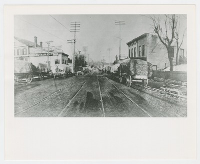 Horse drawn wagons carting tobacco on sticks on South Broadway, just below the railroad tracks