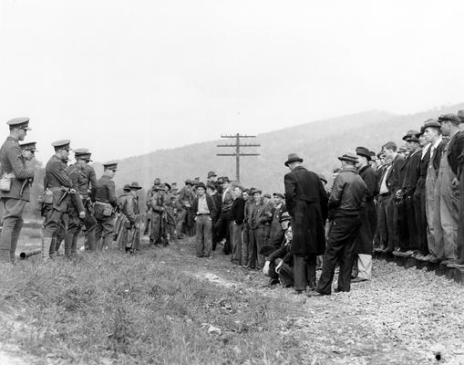 A crowd of miners confronting soldiers