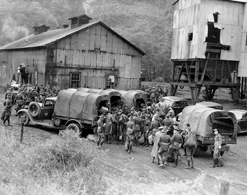 National Guardsmen dismounting from trucks at an assembly point