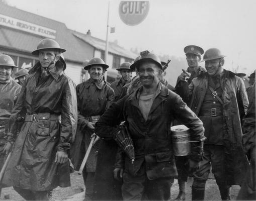 A grinning miner surrounded by National Guardsmen