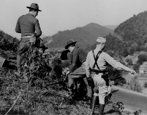 National Guardsmen on a hillside, overlooking a road