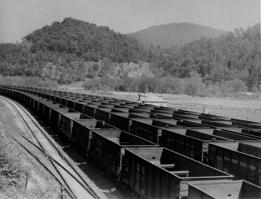 Strings of empty coal cars on railroad tracks