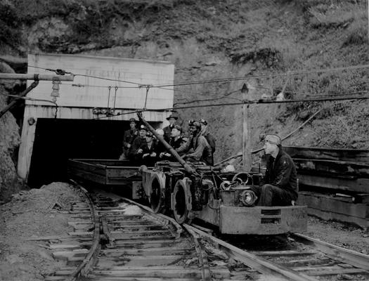 Miners on a mining cart leaving a mine entrance