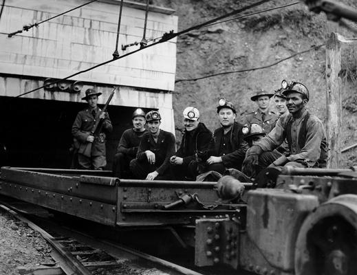 Miners leaving a mine entrance in a cart with police watching