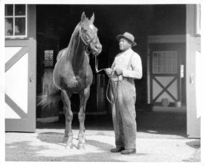Horse and African-American  exercise man at barn;