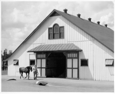 Entrance to a horse barn, with horse and trainer in the foreground