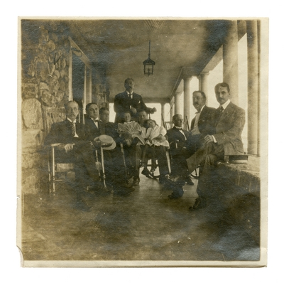 Group portrait of unidentified people on a porch.  Handwritten on verso,