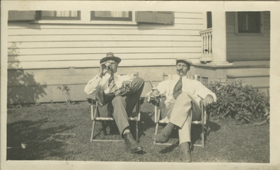Two men in yard; drinking, smoking, and sitting in lawn chairs