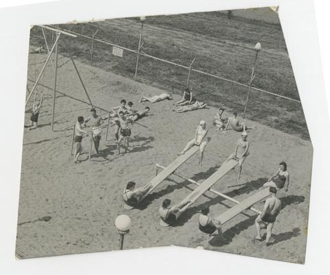 People lounging on playground wearing swimsuit, girls sitting on seesaws, boys leaning against bars, Joyland Park, Lexington, Kentucky