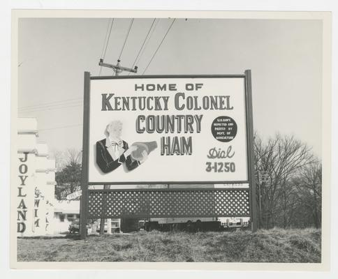 Home of Kentucky Colonel Country Ham Dial 3-1250, sign in ground with man eating ham on it, Joyland Park; advertisement