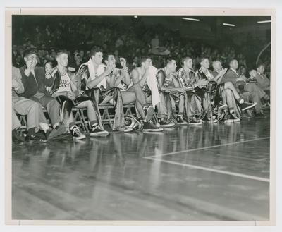 Basketball team on the bench: Frank Ramsey, Bill Spivey, Lou Tsioropoulis, Walt Hirsch, C.M. Newton, Bobby Watson, Shelby Linville, Adolph Rupp, Harry Lancaster