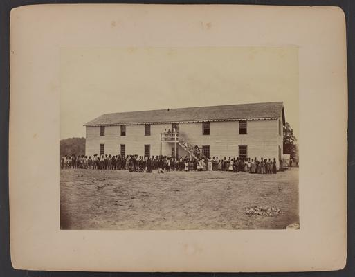 Large posed group photograph; African-American men and women, some men in military uniform in front of large wooden white building