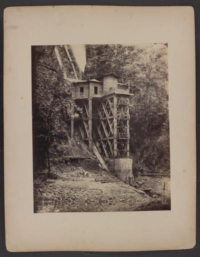 Steam powered pump house; wooden house built on mountainside raised with a concrete structure and wooden beams above the Kentucky River, three people looking out of window, men sitting on porch, trees and wooden staircase going over mountainside in background, creek in foreground