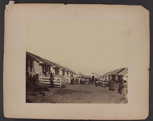 Refugee camp; Street scene; dirt road with small white wooden houses lining both sides far into the distance, crowd of African-American women and children posing in street around man on horse