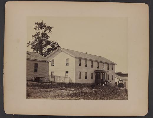 Exterior of building; large white wooden sided building flanked by smaller buildings, two African-American men in front, one on horseback