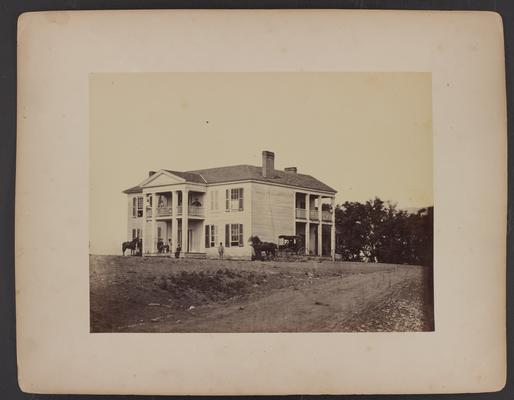 The Oliver Perry House, also known as the White House, the house is a large white wooden sided building with two floors and columns, there are various African-Americans siting on upstairs and downstairs porches, Caucasian man in military uniform sitting on porch, horse, and horse and buggy in front of house, dirt road in foreground, with trees in the background
