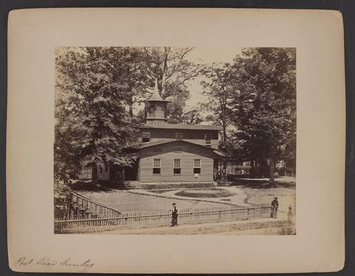The Post Headquarters; wooden building with two floors and cupola, two men are standing on sidewalk near wooden fence in foreground, trees and house with wooden fence in background