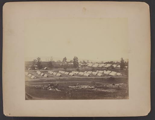 Camp Nelson convalescent camp; eight rows of four white tents each, small group of people sitting in front of them, trees and more tents in background, cleared area and tree stumps in foreground, written on back in pencil, upper left corner, Harmsfeld (?) No 2, on lower left 8 Phelps 3a (?)
