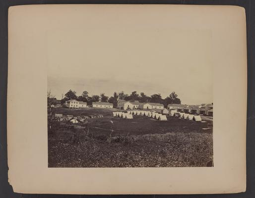 Landscape with building; three rows of white tents with wooden buildings behind them and two floor white wooden buildings adjacent, field in foreground and trees in background