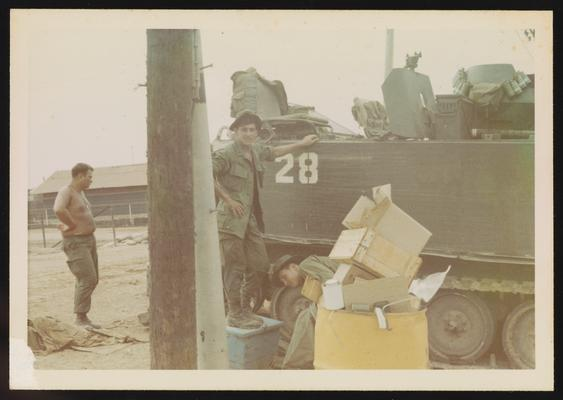 Joe Parisi next to armored personnel carrier in base camp