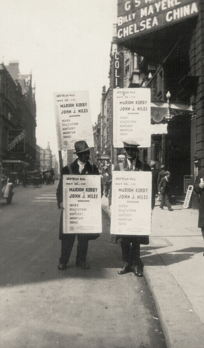 Sandwich-board man advertising a concert by John Jacob Niles and Marion Kerby; London, England
