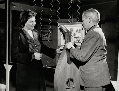 Promotional photo of John Jacob Niles and dulcimer with unidentified woman; Russ Scott, The Flint Journal; Flint, Michigan