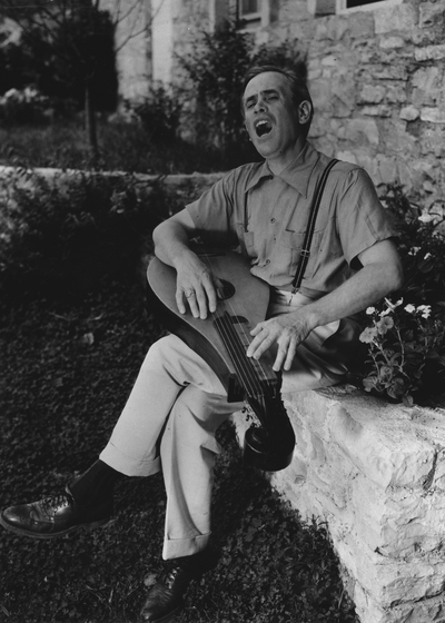 John Jacob Niles outdoors at Boot Hill Farm accompanying himself with dulcimer; National Geographic