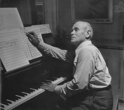 John Jacob Niles at piano, composing