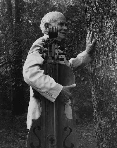 John Jacob Niles standing beside tree with dulcimer; Boot Hill Farm; Pam Sievert, Kentucky Kernel