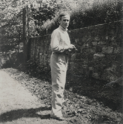 John Jacob Niles standing by a stone wall; Richmond, Virginia