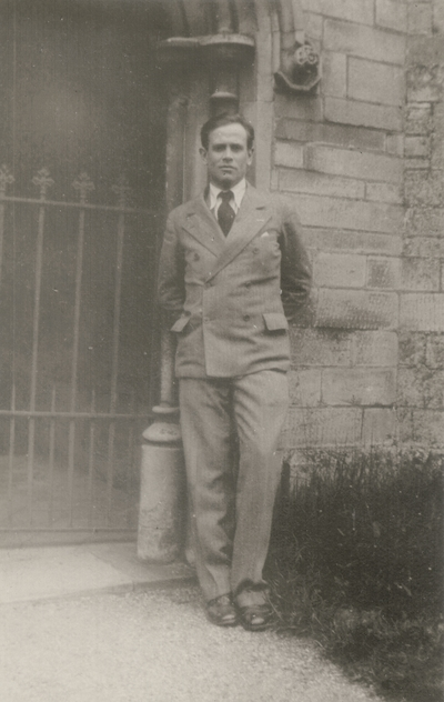 John Jacob Niles standing in from of Christ College state during tour with Marion Kerby; Oxford, England