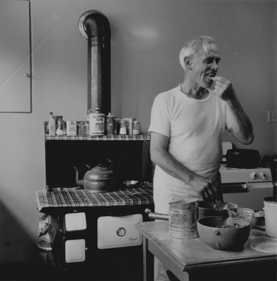 John Jacob Niles in the kitchen making blackberry pie, Boot Hill Farm