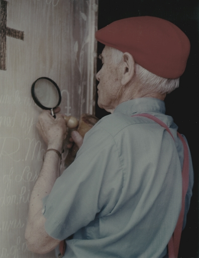 John Jacob Niles puts the finishing touches on carving of doors for St. Hubert's Church; Lexington Herald-Leader
