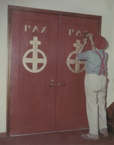 John Jacob Niles puts the finishing touches on carving of doors for St. Hubert's Church