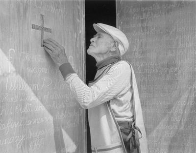 John Jacob Niles puts the finishing touches on carving of doors for St. Hubert's Church; Lexington Herald-Leader