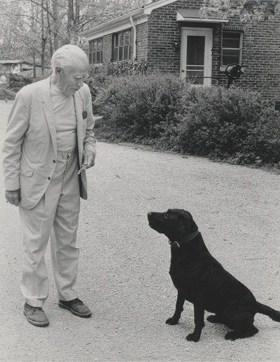 John Jacob Niles outdoors with dog Rosie; Boot Hill Farm; Cincinnati Enquirer