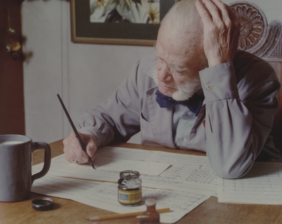 John Jacob Niles working on a music manuscript at dining room table, Boot Hill Farm; Steve Mitchell