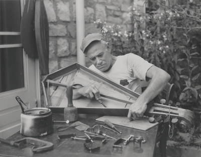 John Jacob Niles outdoors working on dulcimers at Boot Hill Farm; Louisville Courier-Journal