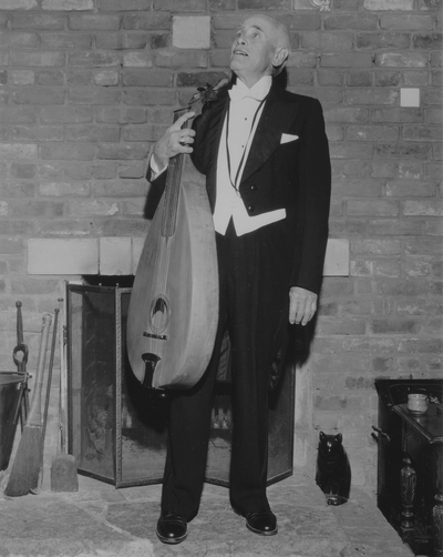 John Jacob Niles in evening dress with dulcimer, posed at Boot Hill Farm; Jack Cobb