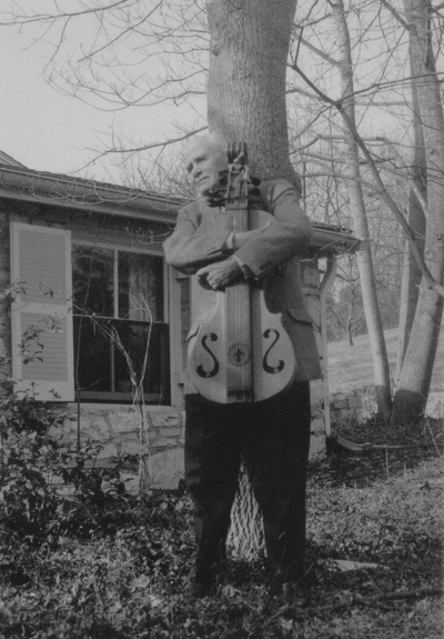 John Jacob Niles outdoors holding dulcimer, Boot Hill Farm; Sallie Aulabaugh