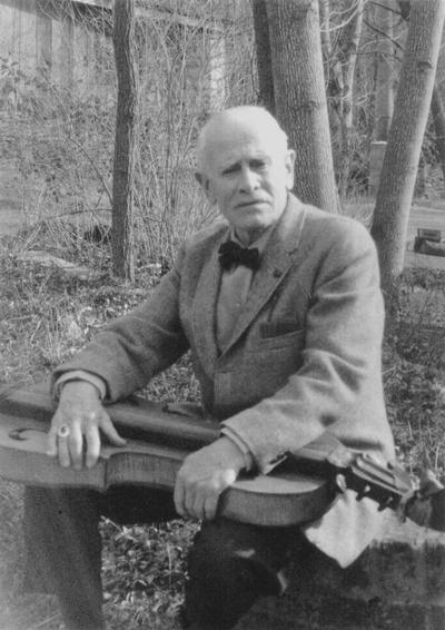 John Jacob Niles outdoors holding dulcimer, Boot Hill Farm; Sallie Aulabaugh