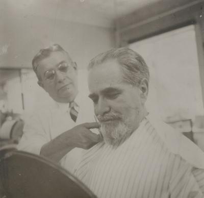 Alphonse Lipetz having his beard trimmed by the Italian barber; Albany, New York
