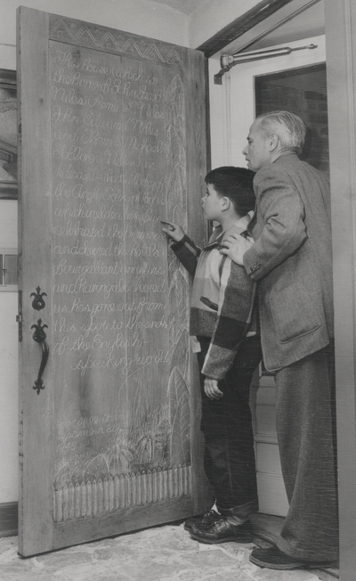 John Jacob Niles with son Tom in front of carved door at Boot Hill Farm